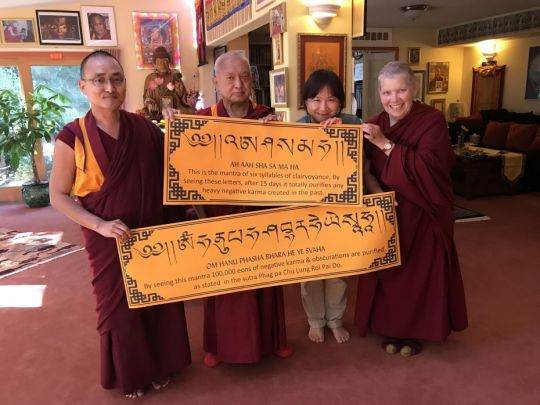 Lama Zopa Rinpoche with Ven. Lobsang Sherab, Monica Hung, and Ven. Carol Corradi with mantra posters, Aptos, California, US, June 2017. Photo by Ven. Roger Kunsang.