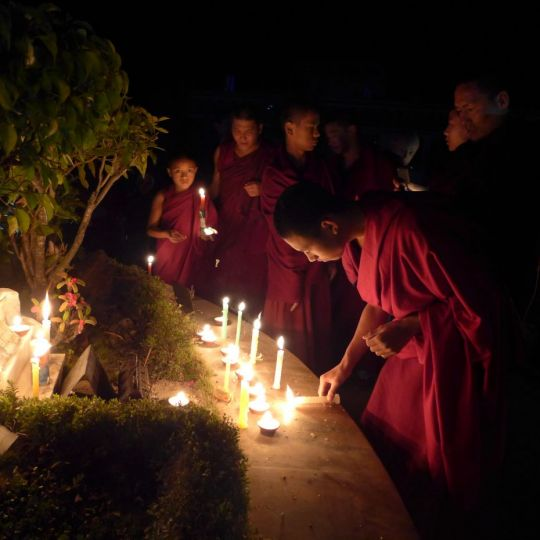 A young monk offers light on Lama Tsongkhapa Day, Kopan Monastery, Nepal, December 2016. Photo by Laura Miller.