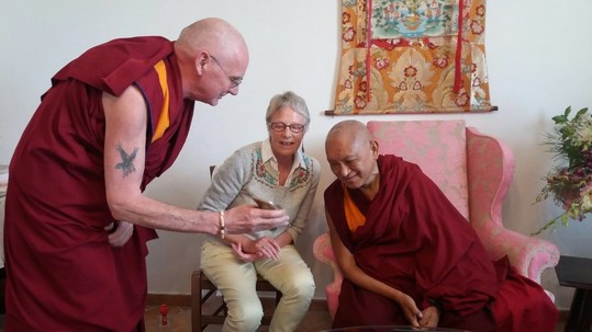 Lama Zopa Rinpoche being shown the Inner Job Description app on a phone with Ven. Roger Kunsang and Wendy Ridley, Istituto Lama Tzong Khapa, Italy, October 2017. Photo by Violette Pilot.