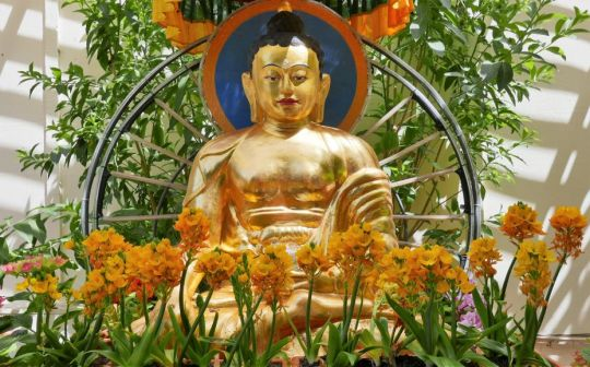 Statue of Buddha with flower offerings, Kachoe Dechen Ling, Aptos, California, US, August 2017. Photo by Ven. Roger Kunsang.