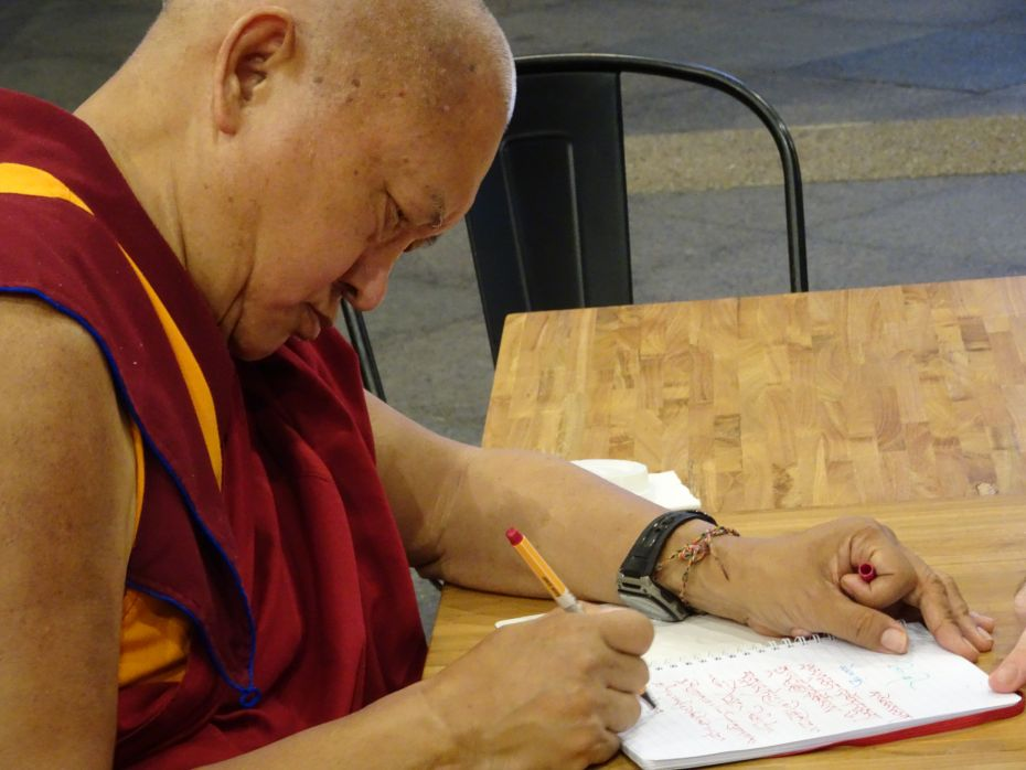 Lama Zopa Rinpoche writing a daily motivation in a monk's diary, Kuala Lumpur, Malaysia, April 2016. Photo by Ven. Roger Kunsang