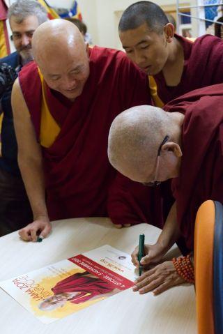 Lama Zopa Rinpoche signing a poster, Istituto Lama Tzong Khapa, Pomaia, Italy, October 2017. Photo by Ven. Lobsang Sherab.
