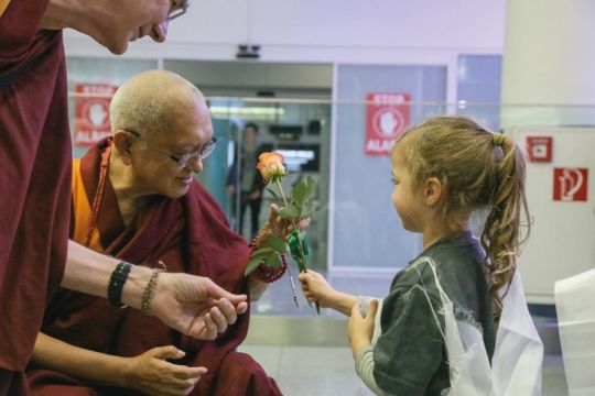 lama-zopa-rinpoche-greeted-by-a-young-person-who-offered-him-a-pink-flower-at-munich-airport-on-the-evening-of-november-3-2018-photo-by-hermann-wittekopf