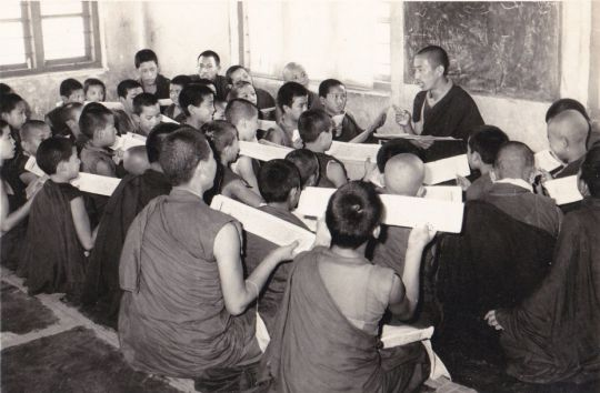 geshe-sonam-gyaltsen-also-known-as-geshe-dhonden-standing-in-the-front-of-a-classroom-in-the-year-1979-teaching-seated-young-monks-in-mundgod-india-photographer-unknown