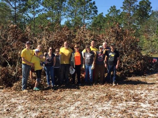 hurricane-florence-relief-work-volunteers-posing-for-a-group-photo-in-front-of-a-pile-of-cleared-branches-in-north-carolina-on-october-12-2018-photo-courtesy-of-kadampa-center