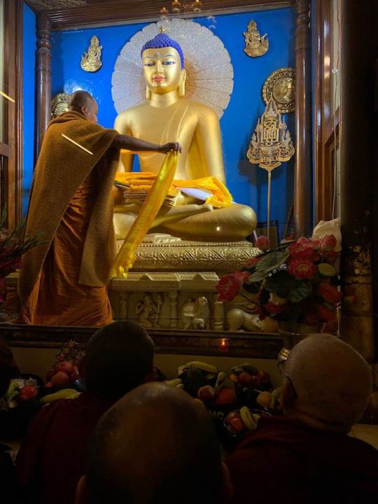 Offering robes to Buddha Mahabodhi Stupa 201901 photo Bill Kane