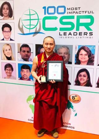 Geshe Tenzin Zopa posing in front of a World CSR Day backdrop that says 100 most impactful CSR leaders with profile photos of the leaders on it with Geshe Tenzin Zopa holding his trophy and framed award certificate
