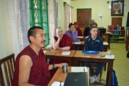 Geshe Tenzin Wangdak smiling while teaching Lotsawa Rinchen Zangpo Translation Program students seated at tables in Dharamsala classroom