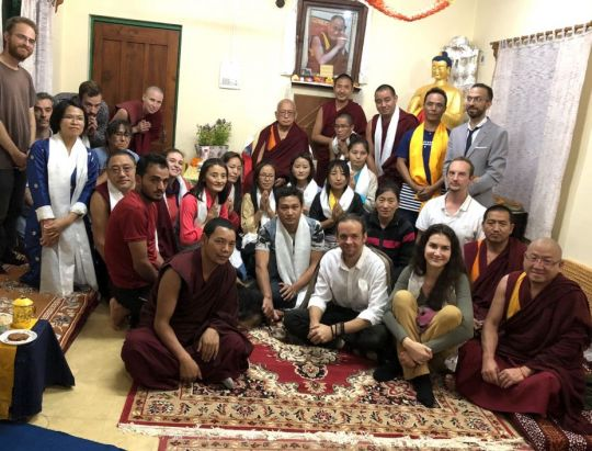Lama Zopa Rinpoche surrounded by 28 students and teachers, posed and smiling for the camera