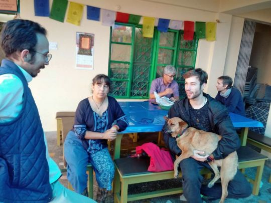Teacher Mr. Alejandro M. Garcia talking outside with two students seated on a picnic table, with brown dog Christabella in the arms of one of the students