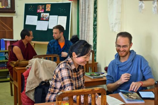Two groups of students talking while referring to papers on the tables in front of them, smiling and enjoying their studies