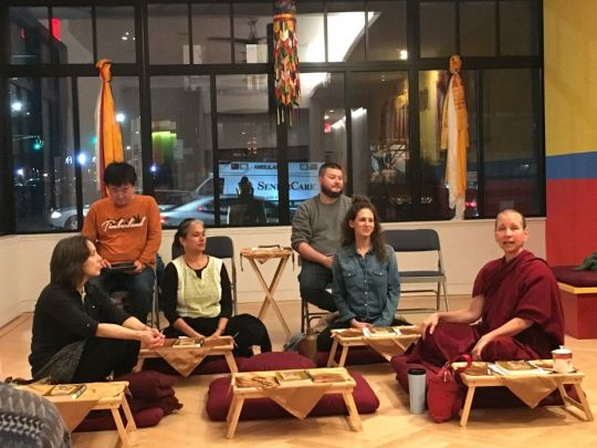 Venerable Amy Miller sitting with a small group of students in the Shantideva Center gompa