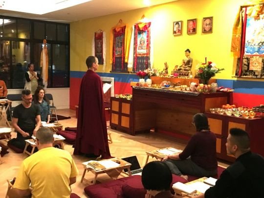 Venerable Amy Miller standing facing the altar in the Shantideva Center gompa