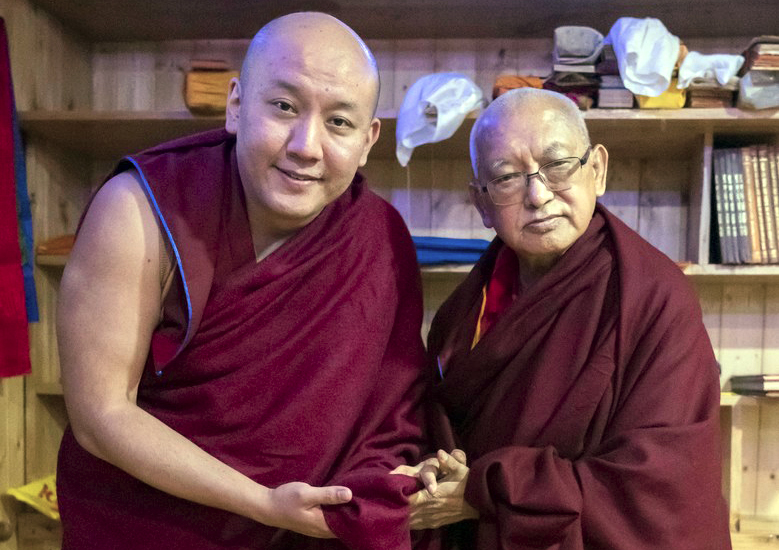 Zong Rinpoche and Lama Zopa Rinpoche holding hands and posing for the camera in front of bookshelves containing Dharma items inside at Tushita Meditation Center in Dharamsala