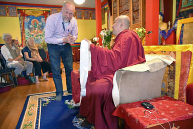 Maarten de Vries standing in front of a seated Zong Rinpoche smiling at the camera and receiving a khata