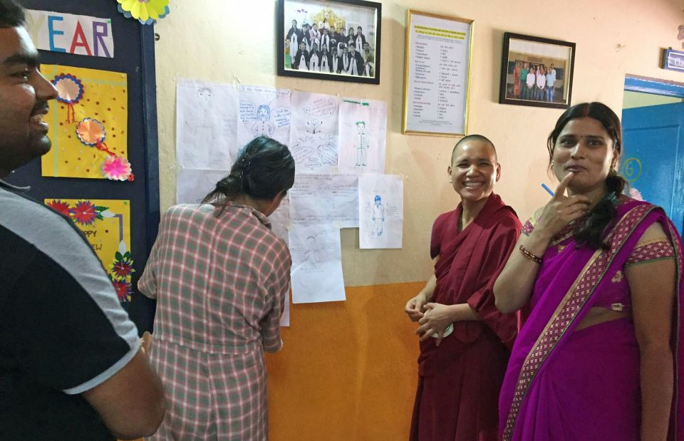 Four members of the maitreya school staff engaged in a fun workshop activity where they were writing on a big piece of white paper hanging on the school auditorium wall.