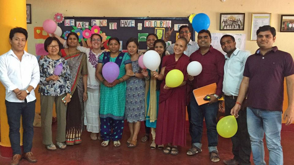 Maitreya school teachers and workshop facilitators standing the school auditorium holding brightly colored balloons and standing in front of a colorfully decorated school bulletin board.