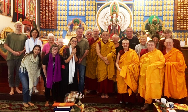 Students standing together posing for the camera in front of the Chenrezig statue in the Chenrezig Institute gompa