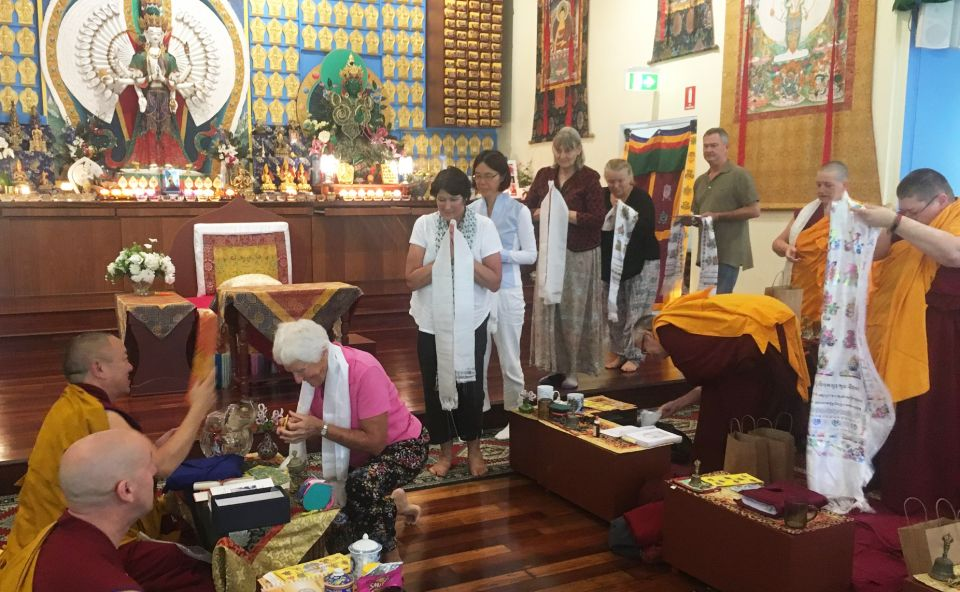 Students offering khatas to Geshe Phuntsok Tsultrim in the Chenrezig Institute Gompa