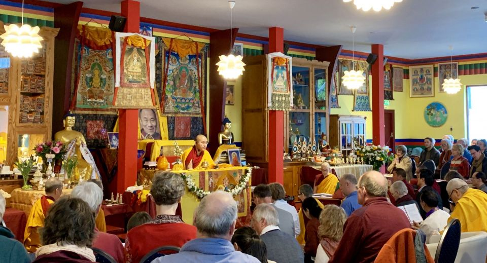 Ling Rinpoche seated at the front of a colorful gompa teaching a room full of students at Maitreya Instituut Loenen