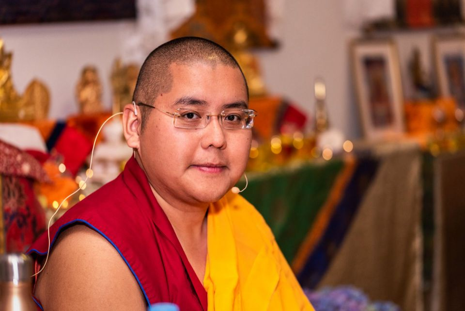 Ling Rinpoche seated in a gompa in Madrid smiling into the camera.