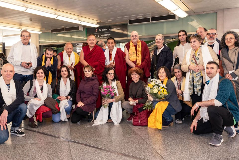 Ling Rinpoche posing for a photo with students holding flowers at a station in Madrid Spain.