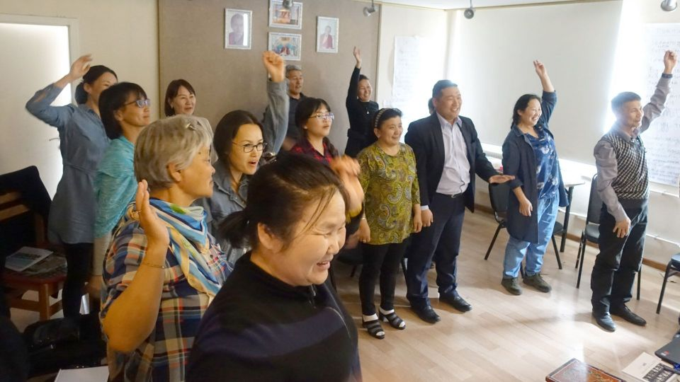Room of people enthusiastically throwing their arms up in the air while doing a fun activity.