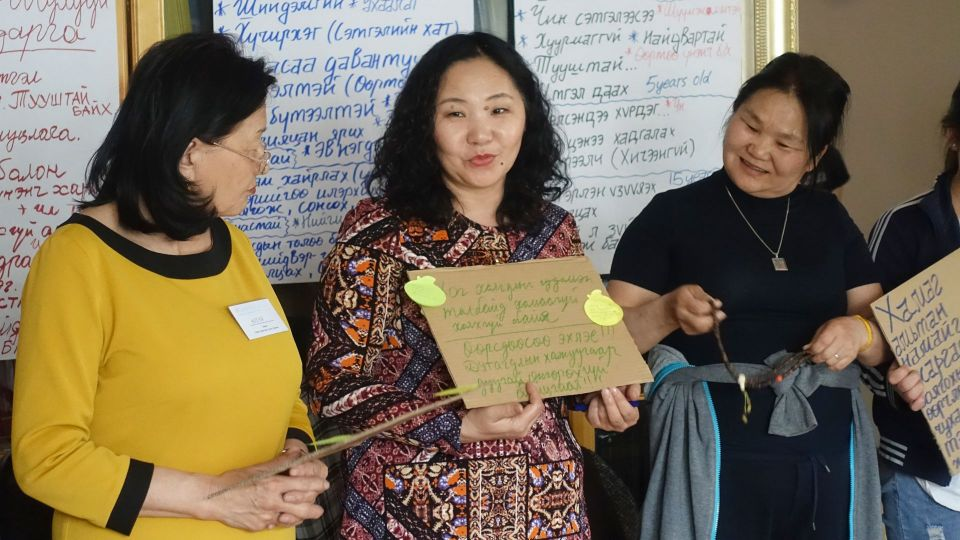 One group activity participant holding a sign handwritten on a small piece of cardboard while two other participants look on and smile.