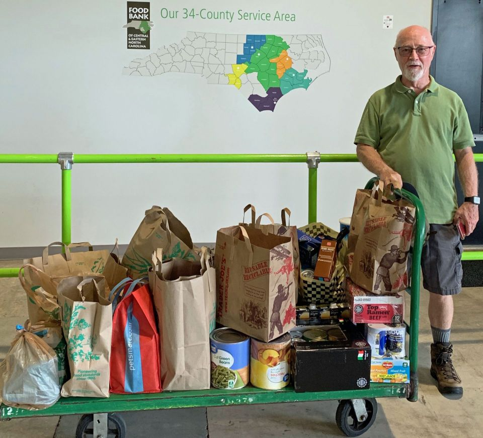 A kadampa center volunteer standing next to a wheeling cart full of bags of donated food most of it still inside of the grocery store brown paper grocery bags and standing in front of a wall that has a map of north carolina showing the areas served by the north carolina food bank.