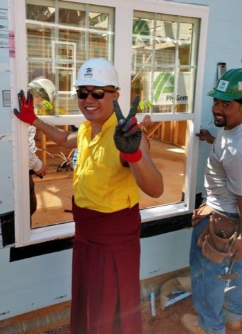 Geshe palden sangpo dressed in his monks robes wearing a white construction hardhat and black gloves and making a peace sign with his left hand while he works on a window frame on a habitat for humanity house construction project.