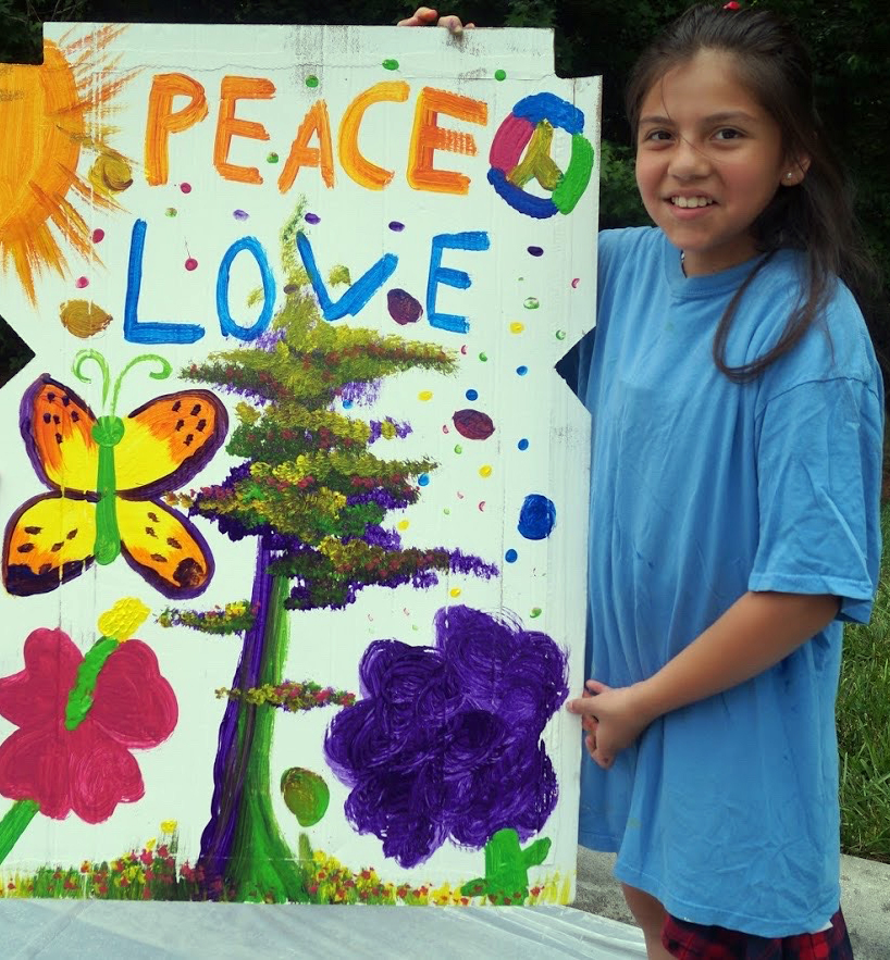 A young person proudly holding up a painting they made on a large piece of cardboard that says peace and love and has paintings of a tree flowers butterfly peace sign and the sun on it.