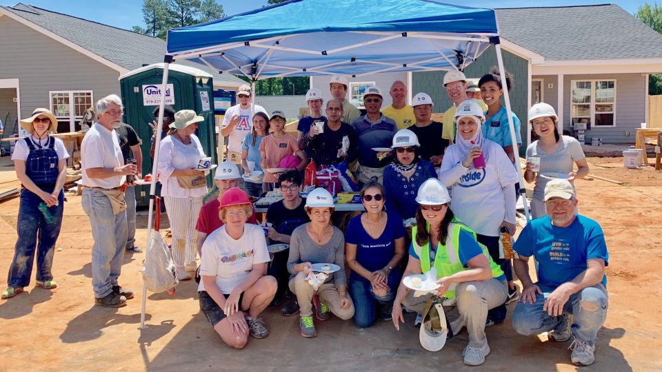 A group of volunteers posing for the camera on a habitat for humanity construction site with sawhorses tools and a building under construction in the background of the photo.