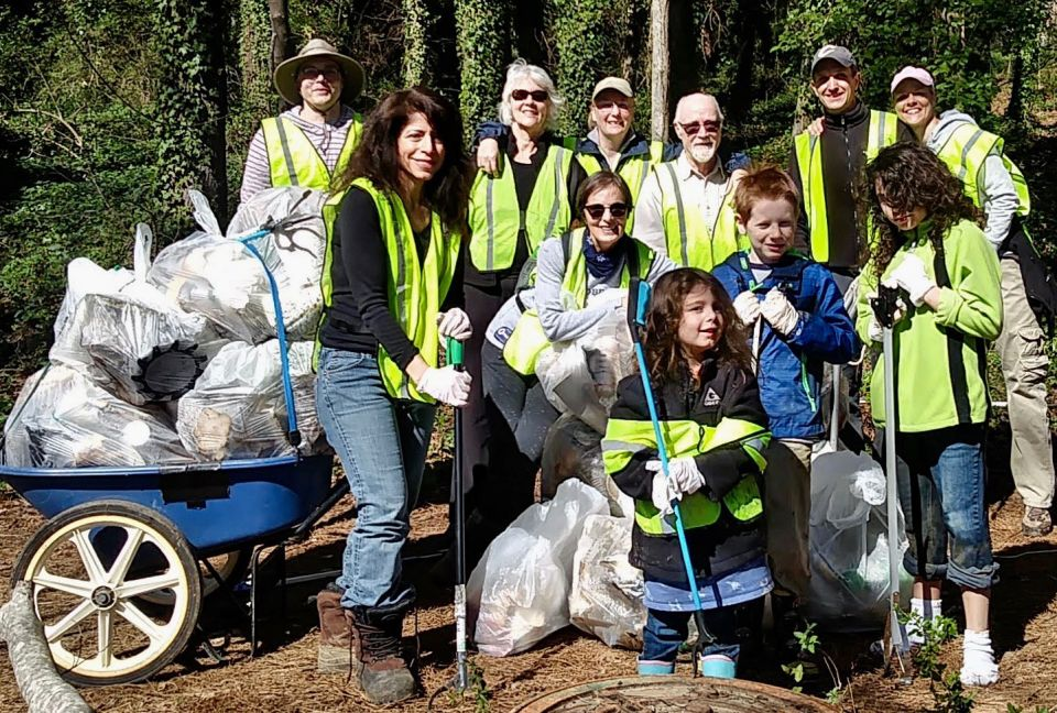 A group of people ranging in age from small children to older adults dressed in bright yellow construction vests and standing next to a wheelbarrow full of plastic garbage bags of trash they collected with a forest of trees in the background.