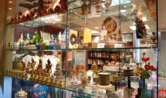Gold colored statues and assorted beautiful items on glass shelves in the Amitabha Buddhist Centre shop