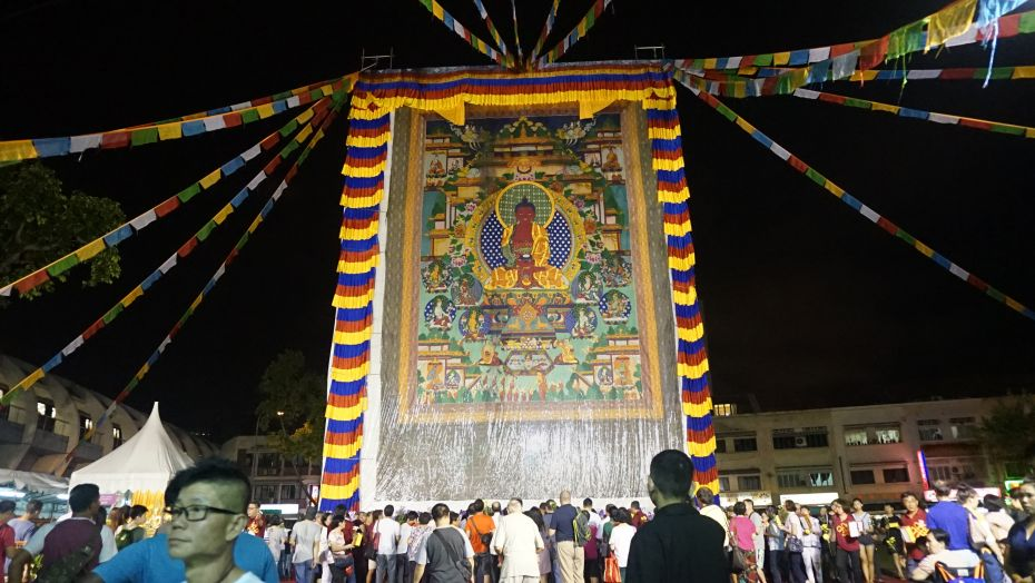 A crowd of people viewing a huge Buddha thangka outside Amitabha Buddhist Centre