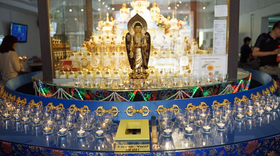 Buddha statue surrounded by candle light offerings at Amitabha Buddhist Centre in Singapore