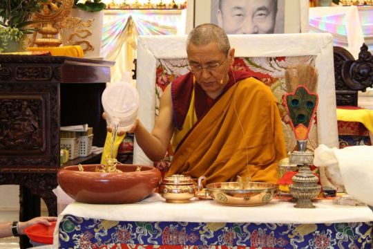 Khen Rinpoche Geshe Chonyi seated at the front of the Amitabha Buddhist Centre gompa making offerings