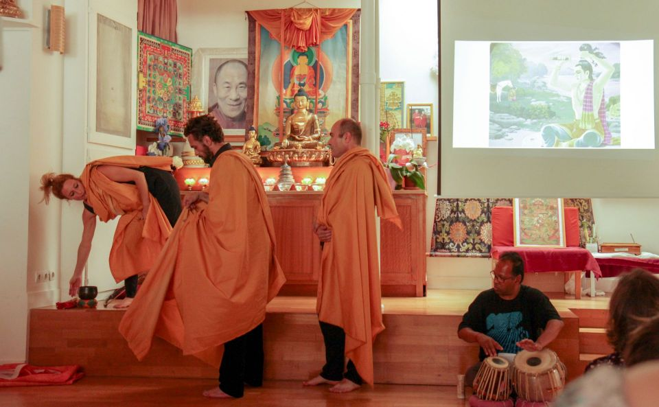 Three performers dressed in golden colored monks robes enacting a scene while a fourth person sits on the ground playing a set of drums by hand.