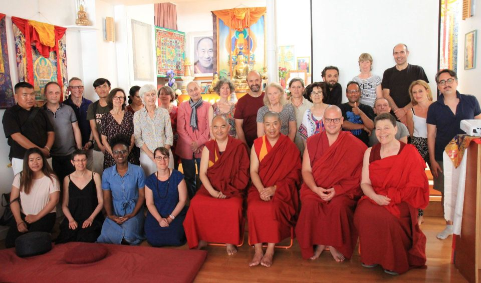 29 people posing for a group photo in front of the altar at kalachakra center in paris france.