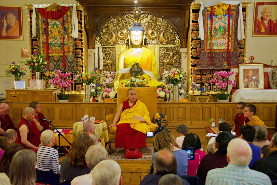Ling Rinpoche seated on a gold colored chair in the front of the Jamyang Buddhist Centre London altar teaching an audience of students.