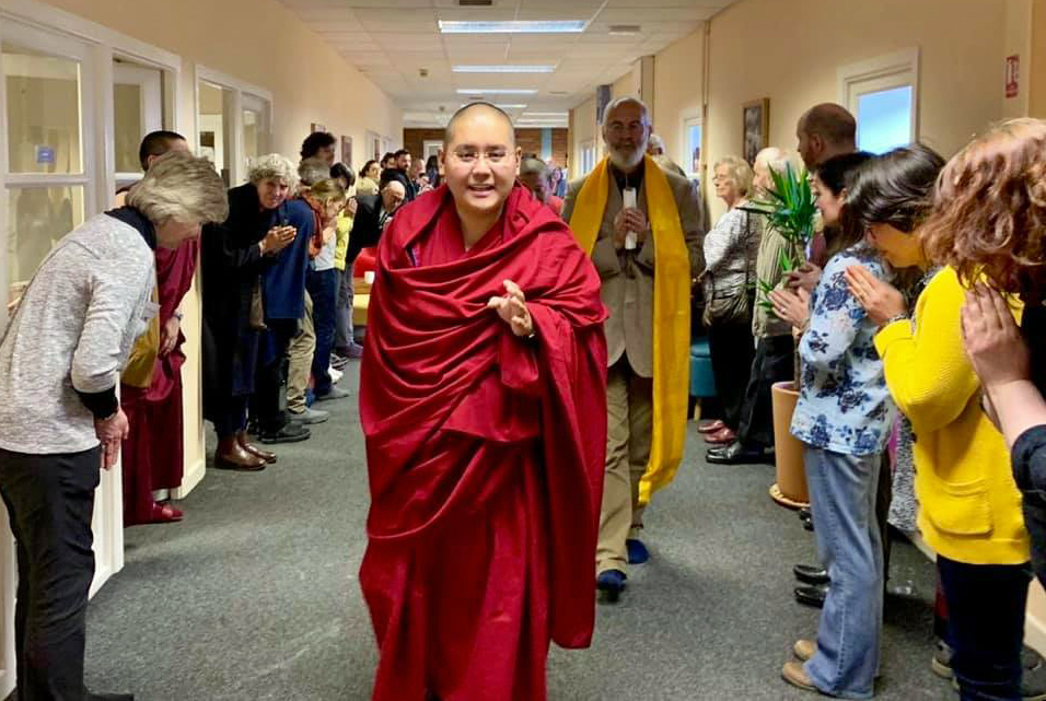 Ling Rinpoche walking down a hallway lined with students bowing holding khatas and approaching the camera smiling.