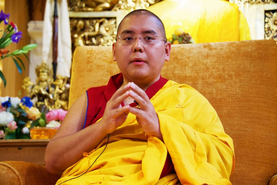 Ling Rinpoche seated with hands clasped on a golden colored chair at the front of the gompa at Jamyang Buddhist Centre London.