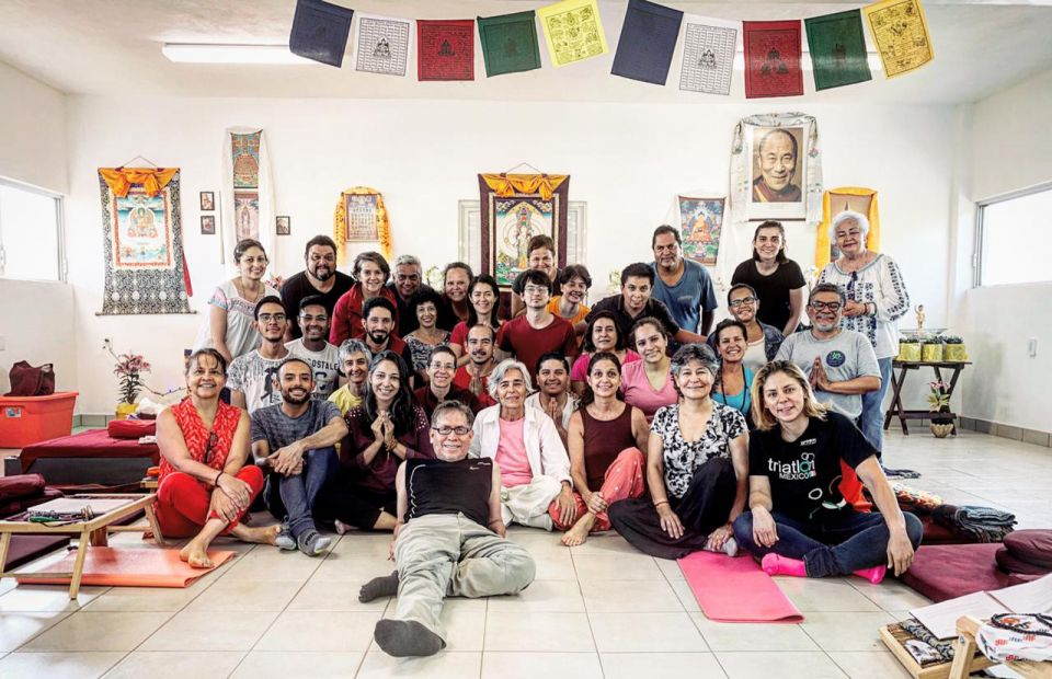 Large group of students posing with Ven. Thubten Norbu for a photo in front of the altar with bright colored prayer flags hanging from the ceiling above the smiling group.