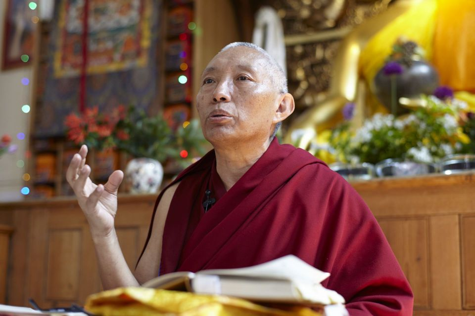 geshe tashi tsering seated in front of a large Buddha statue teaching in the gompa at jamyang buddhist center in london with his right hand raised and hand open as if making a gesture.