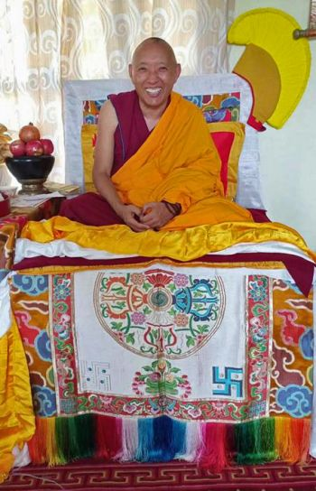 geshe tashi tsering seated on a beautiful colorful tibetan style throne with a big smile on his face.