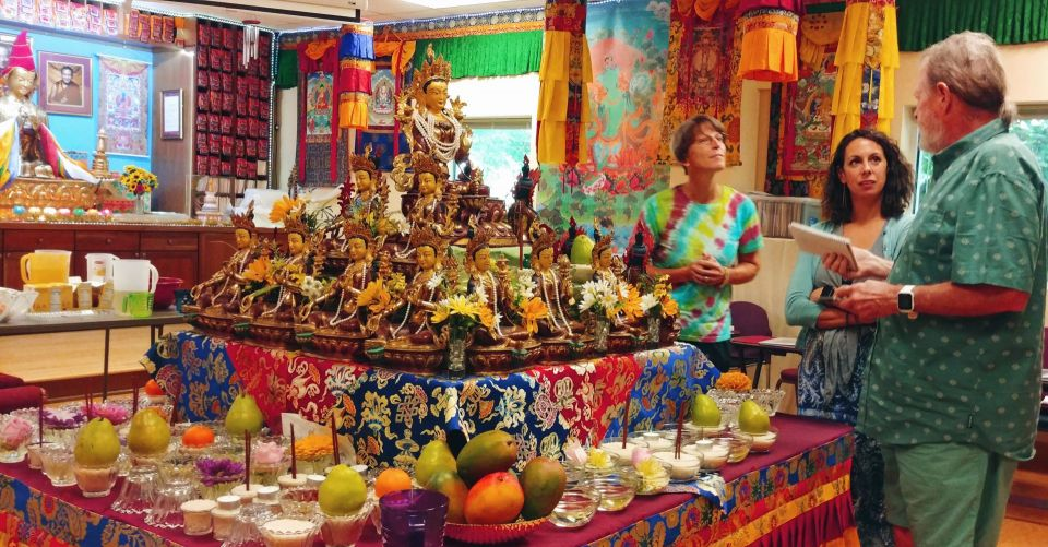 Three people standing around a medium sized table covered in Tibetan fabrics and offerings with 21 beautiful statues of Tara in a pyramid formation in the center of the table.