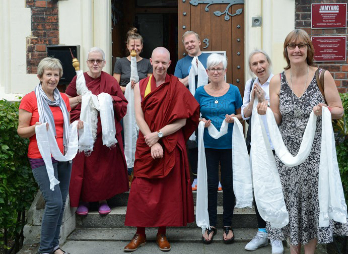 Geshe Tenzin Namdak standing with seven people holding khatas and smiling for the camera while standing outside on the jamyang buddhist center london building steps.