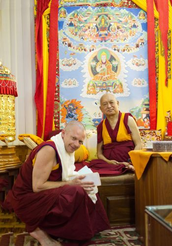 Geshe Tenzin Zopa kneeling at the feet of Lama Zopa Rinpoche. Geshe Namdak has a white khata around his neck and his hands folded together while Lama Zopa Rinpoche is seated on low but raised seat and smiling.