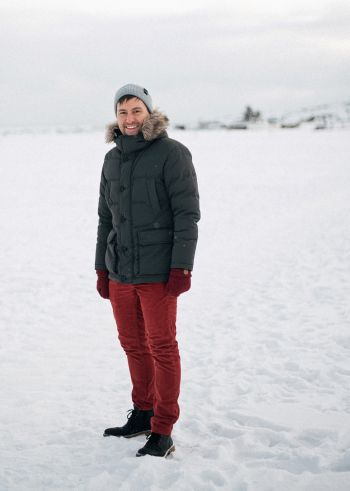 joona repo standing on the frozen sea wearing a winter jacket and maroon pants hat and gloves smiling at the camera in front of a snow covered background with a grey sky.