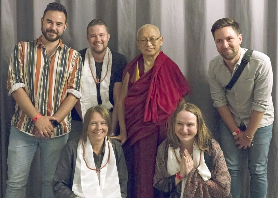 Lama Zopa Rinpoche smiling and posing for a photo with five students backstage in front of a grey curtain at the teaching event in Riga Latvia.